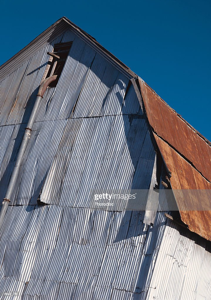 a large white barn with a brown roof stands under a blue sky : Foto de stock