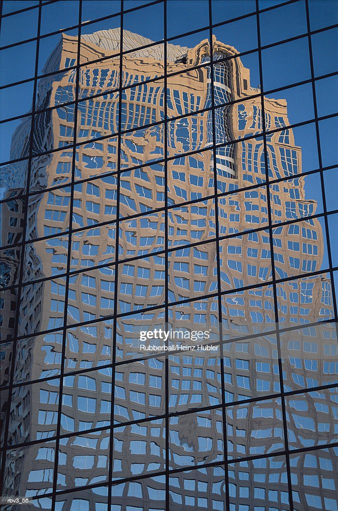 a large windowed beige building is reflected in the glass windows of another skyscraper : Foto de stock