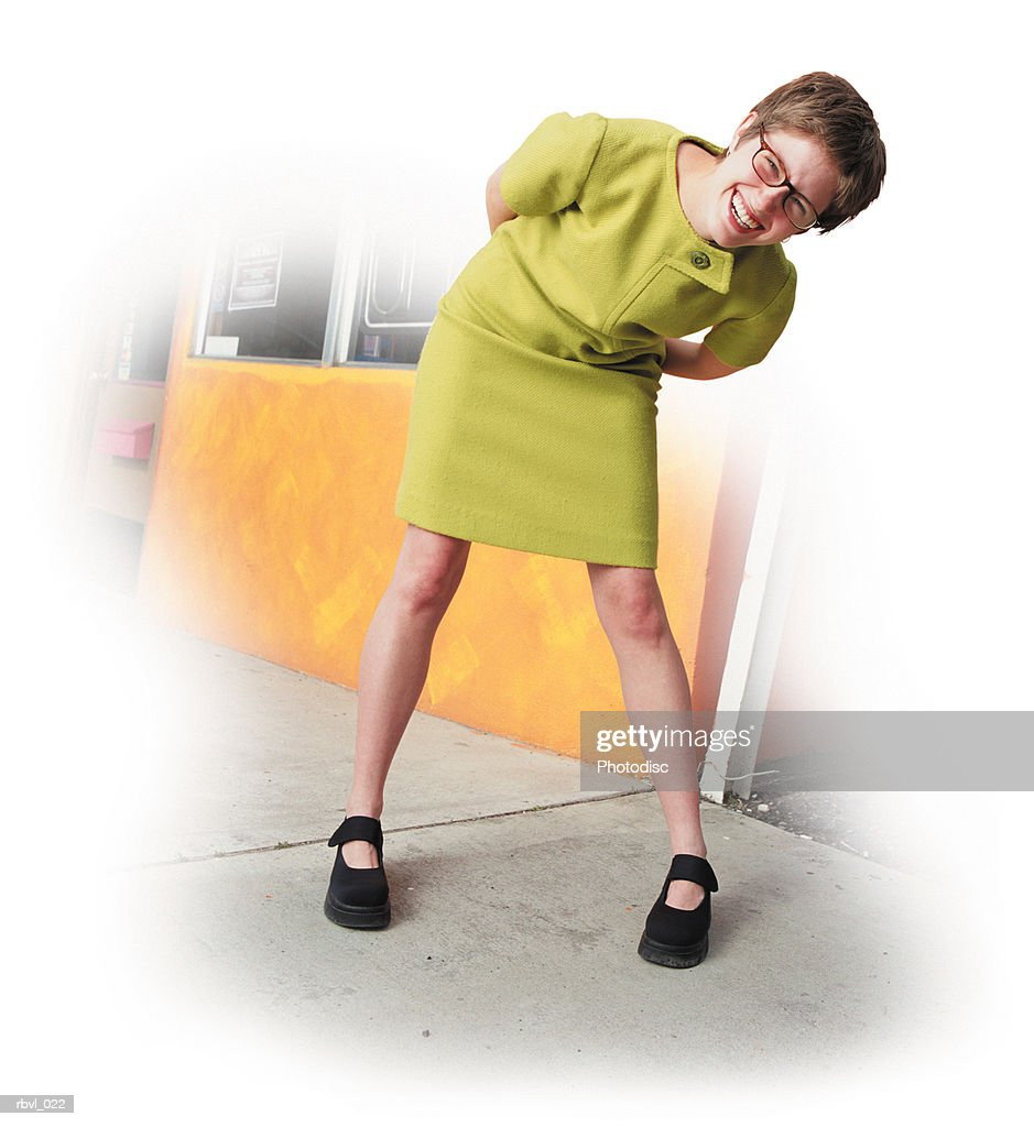 a laughing young caucasian woman in a short trendy green dress is bending down to look into the camera with an orange building in the background : Foto de stock