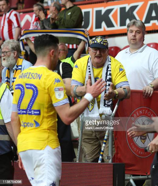 a Leeds supporter consoles Jack Harrison of Leeds United after the Sky Bet Championship match between Brentford FC and Leeds United at Griffin Park...