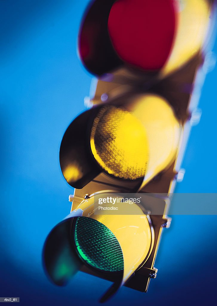 a lit red and yellow and green traffic light on top of a blue background : Foto de stock