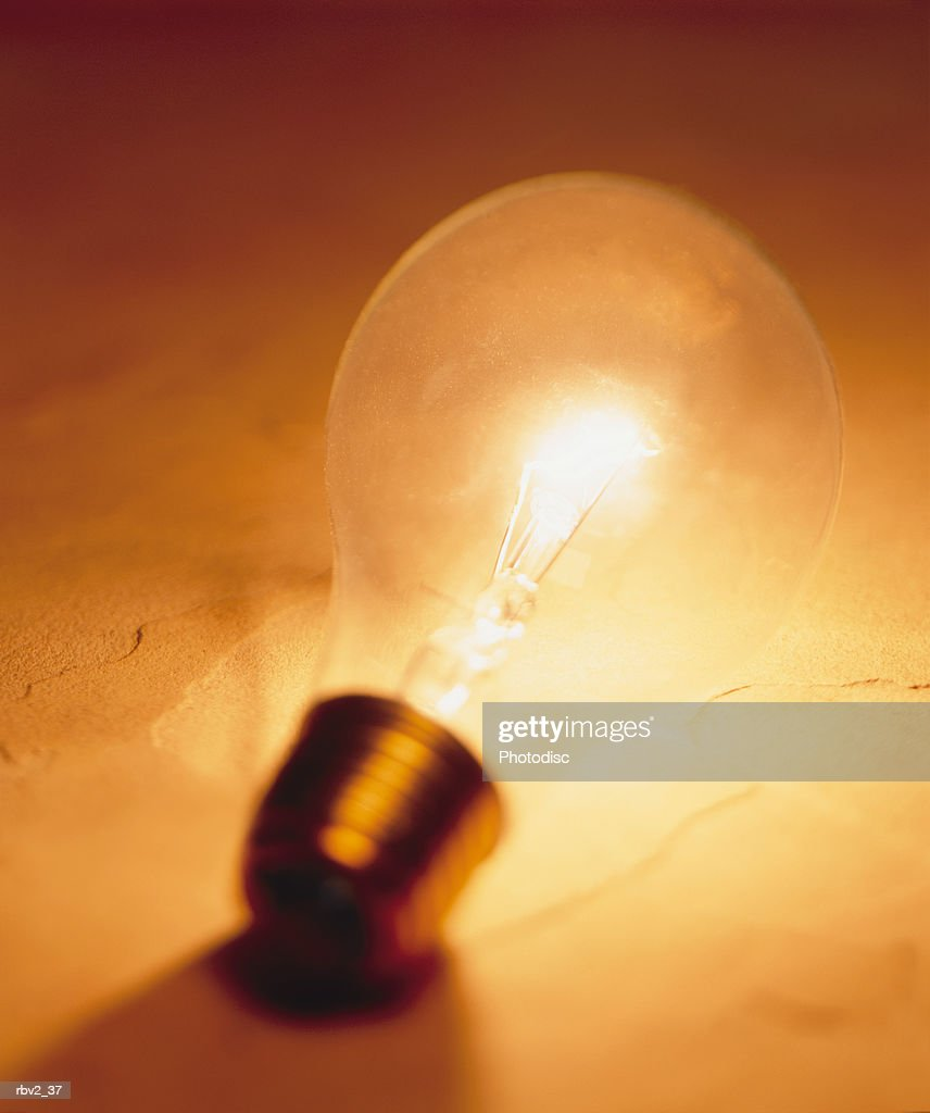 a lit unscrewed lightbulb casts a shadow as it sits on a gold surface : Foto de stock