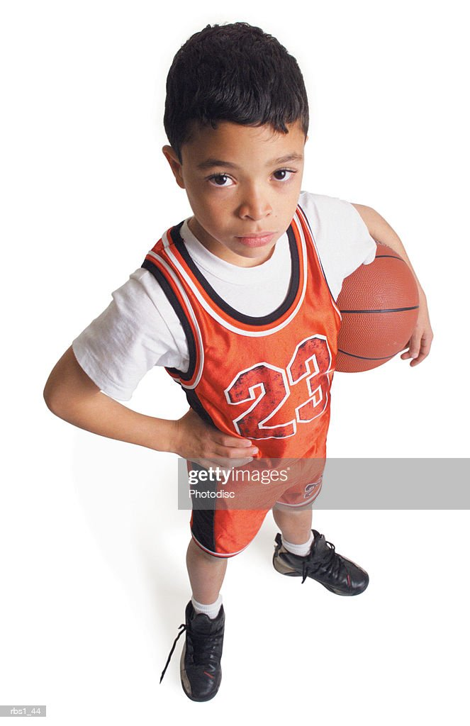 a little african american boy wearing a red basketball uniform is standing looking up at the camera holding a basketball under his arm : Foto de stock