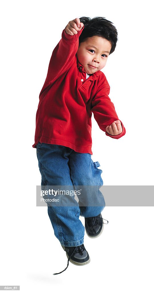 a little asian boy in a red shirt  jumps up and throws his arms forward : Stockfoto