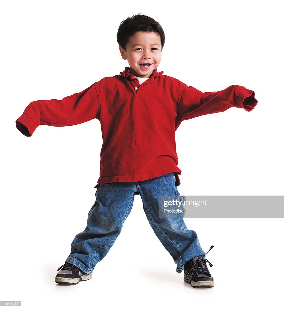 a little asian boy in a red shirt with long sleeves stand with his arms out and feet spread apart laughing : Stock Photo