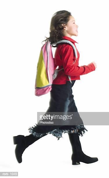 a little asian girl in a black skirt and red shirt with a backpack runs to school
