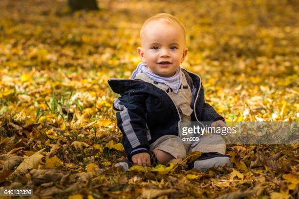 a little baby boy sitting on the ground in autumn