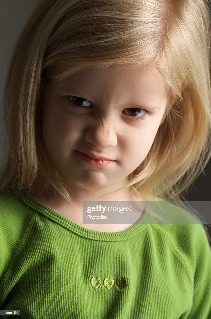 a little blond girl in a green shirt scrunches her nose in an expression of annoyance : Stockfoto