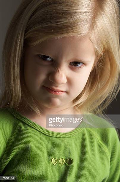 a little blond girl in a green shirt scrunches her nose in an expression of annoyance - ugly girl stock photos and pictures