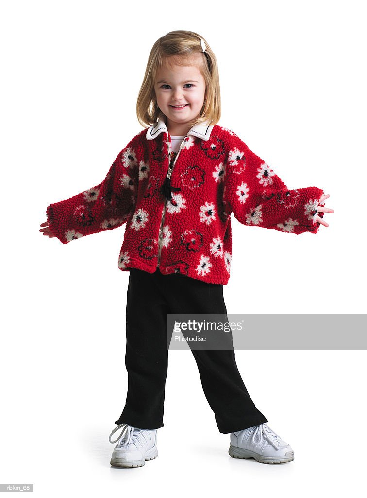 a little blonde girl in a red flower patterned sweater smiles and holds her arms open : Stockfoto