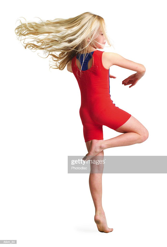 a little blonde girl in a red gymnastics outfit spins rapidly around as dances : Stockfoto