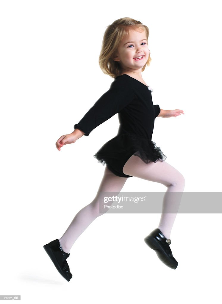 a little blonde girl in tights and a dance outfit runs forward playfully smiling : Stockfoto