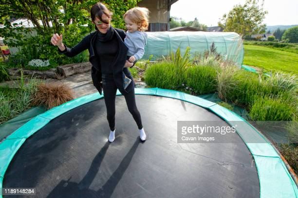 a little boy and his mom playing on a trampoline in the country side, caurel brittany, france. - individual event stock pictures, royalty-free photos & images