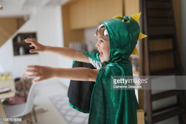 a little boy dressed as a dinosaur playing in the kitchen - mask disguise stock pictures, royalty-free photos & images