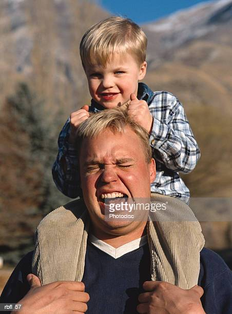 a little boy on his dad's shoulders pulls his hair and smiles