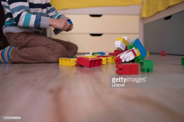 a little boy playing with colored cubes on the floor - servizi per l'infanzia foto e immagini stock