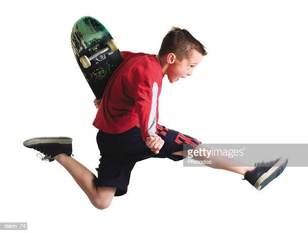 a little caucasian boy in a red shirt flies through the air while clutching his skateboard