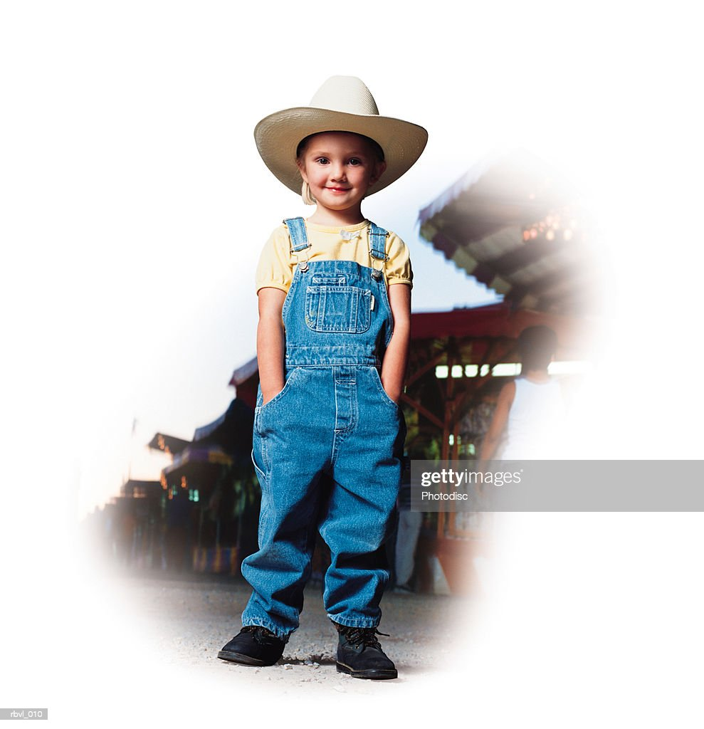 a little caucasian girl in blue overalls and a yellow shirt and a white cowboy hat is standing at a county fair : Foto de stock