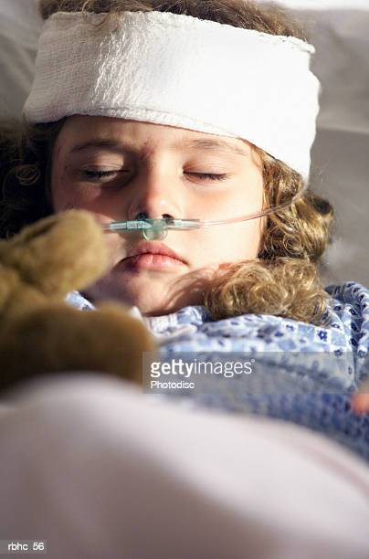 a little caucasian girl lies in a hospital bed recovering from a head injury