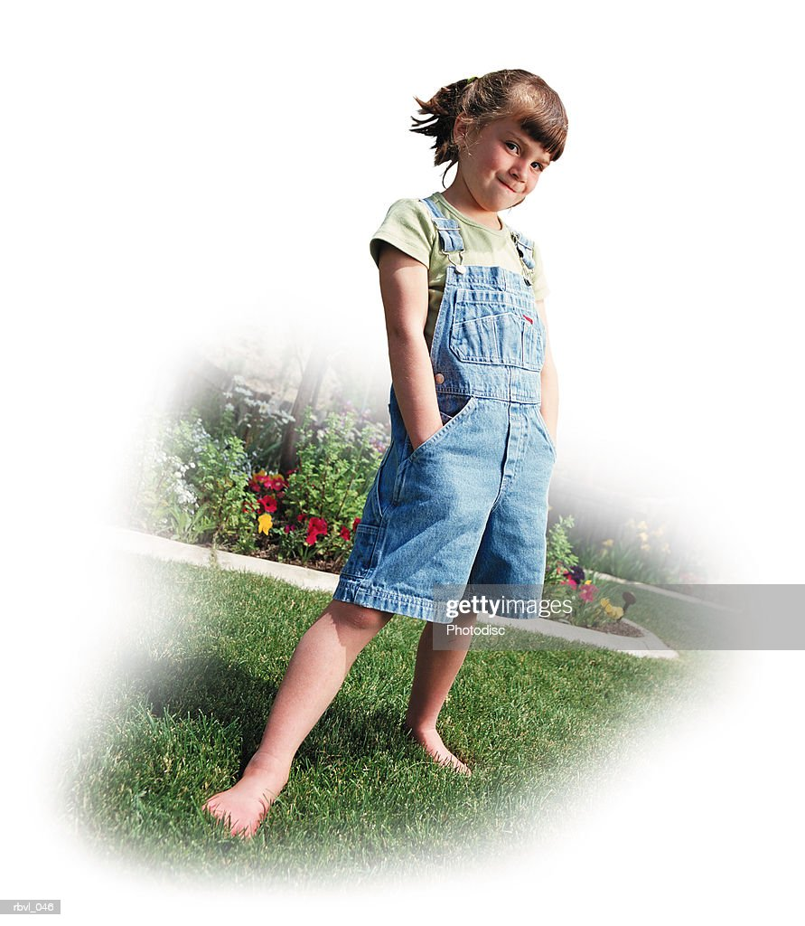a little caucasian girl with a ponytail is wearing short overalls with her hands in her pockets as she stands on a lawn bordered by flowers : Foto de stock