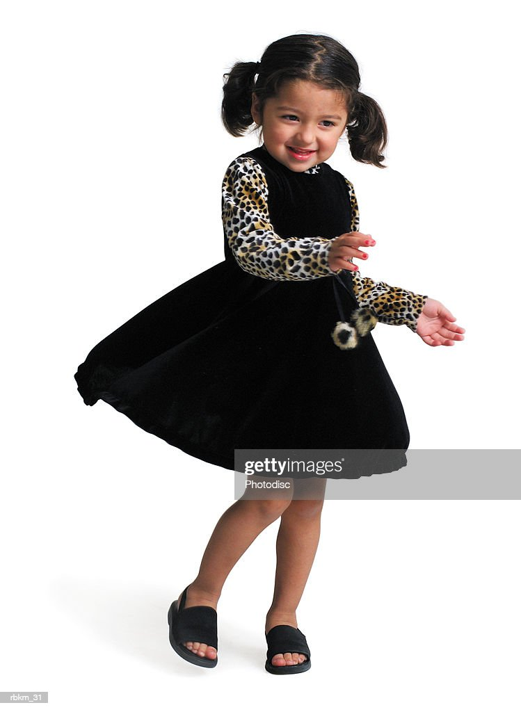 a little ethnic girl in a black dress with leopard print sleeves spins and dances while smiling : Stockfoto