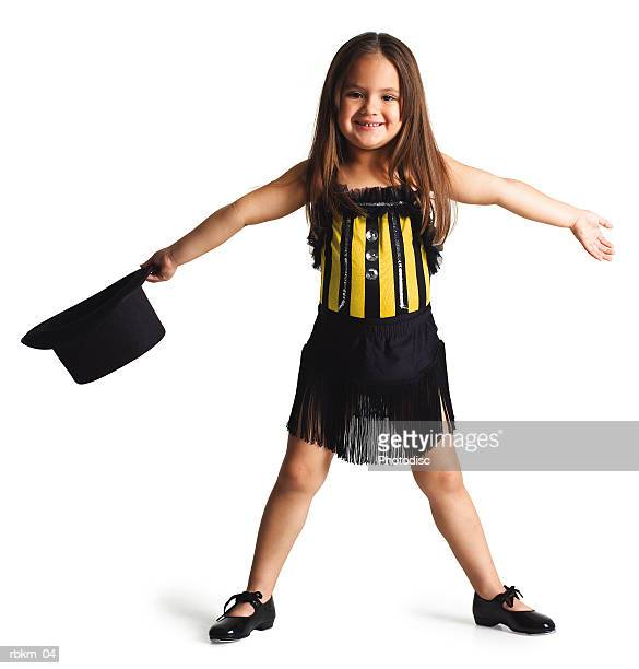 a little ethnic girl in a dance outfit spreads her arms out and smiles while holding a top hat