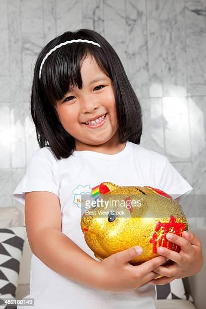 a little girl holding a piggy bank