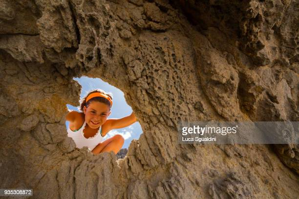 a little girl looks out from a hole in the lava rock, smiling at camera