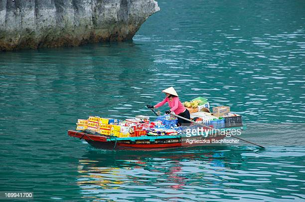 A local woman selling groceries from a boat in World-Heritage Ha Long Bay, Vietnam