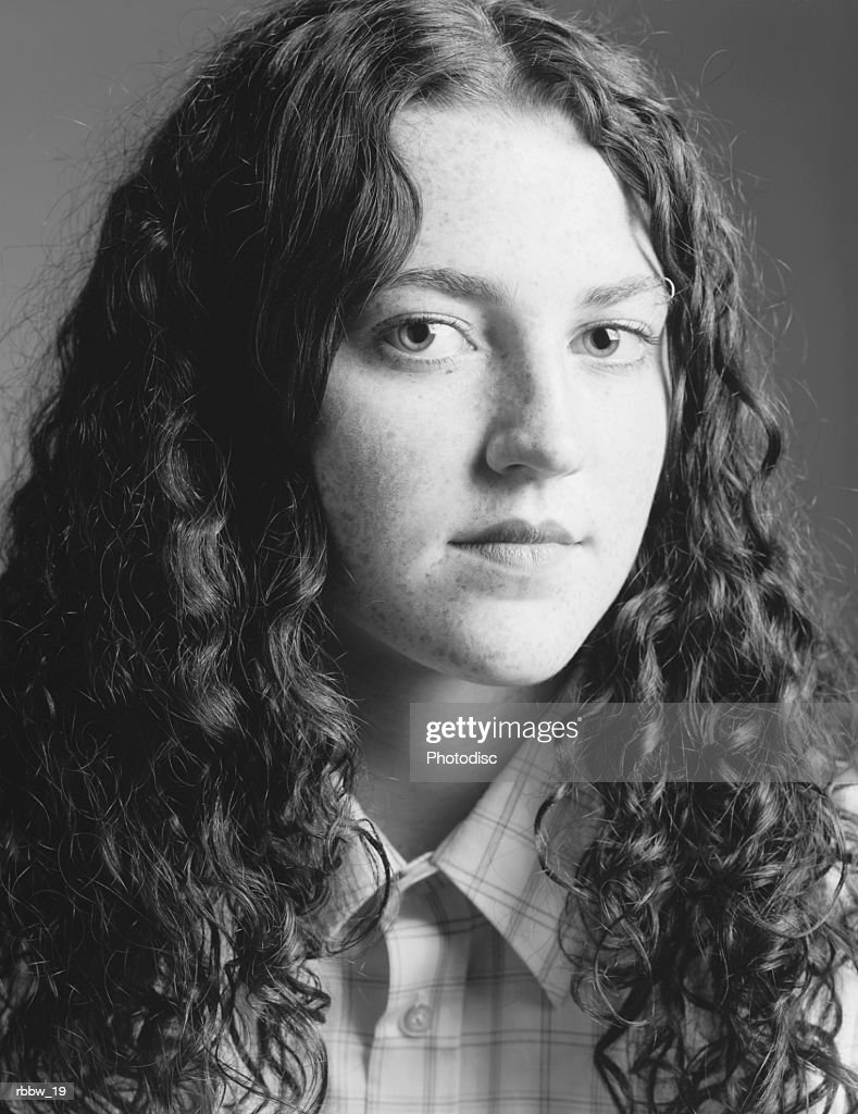 a long curly haired caucasian teen with attitude glares at the camera : Stockfoto