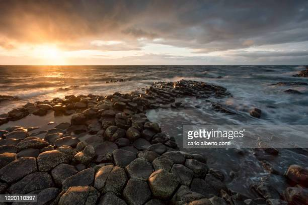 a magical light during summer sunset at causeway giants, ireland - county antrim stock pictures, royalty-free photos & images