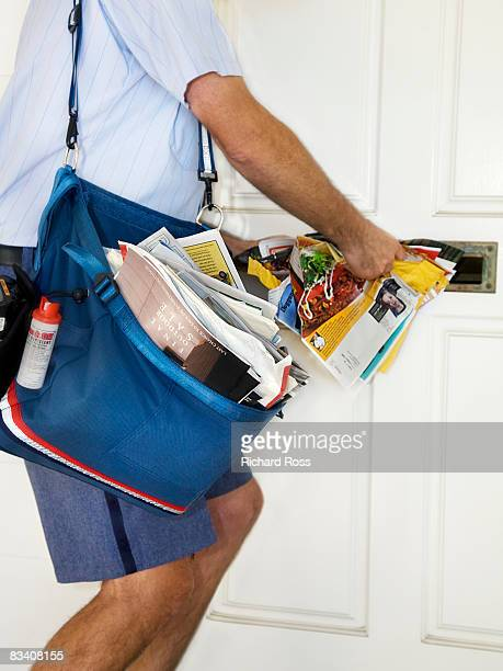 a mailman stuffing junk mail into a mailbox - junk mail stock pictures, royalty-free photos & images