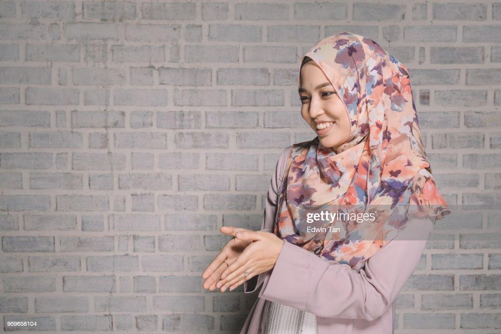 ein malaysischer Weibchen tragen traditionelle Kleidung und Tudung tut ein Gruß Handgeste für Ramadan Saison : Stock-Foto