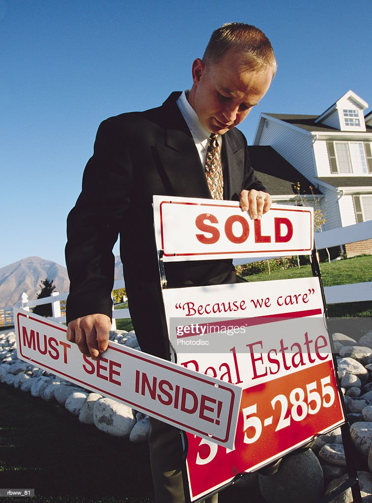 a male caucasian real estate agent stands in front of a house he just sold : Stockfoto