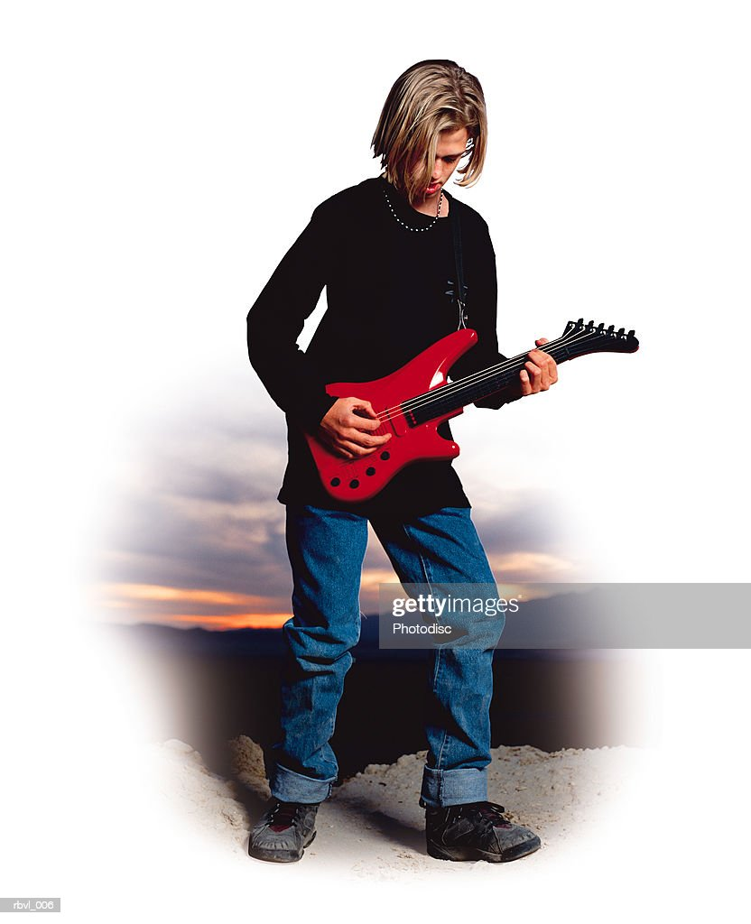 a male caucasian youth with long blond hair wearing a black shirt and blue jeans is standing outside playing an electric guitar : Foto de stock