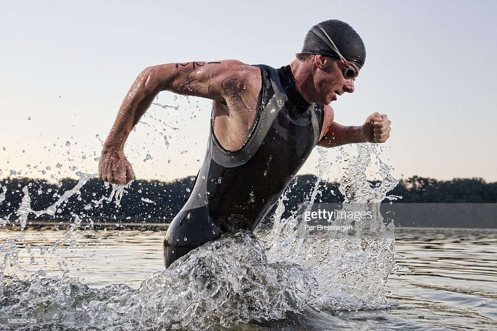 a male triathlete running out of the water : Stock Photo