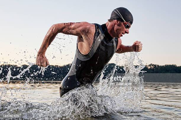 a male triathlete running out of the water