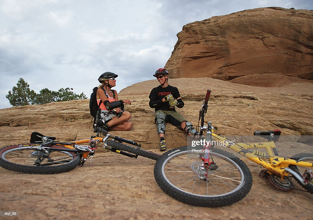 a man and a woman are resting on a rock in moab utah with thier mountain bikes laying down in front of them : Foto de stock