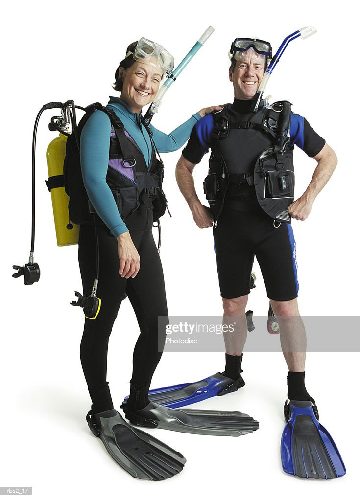 a man and a woman wearing wet suits with fins and snorkles stand together smiling : Foto de stock