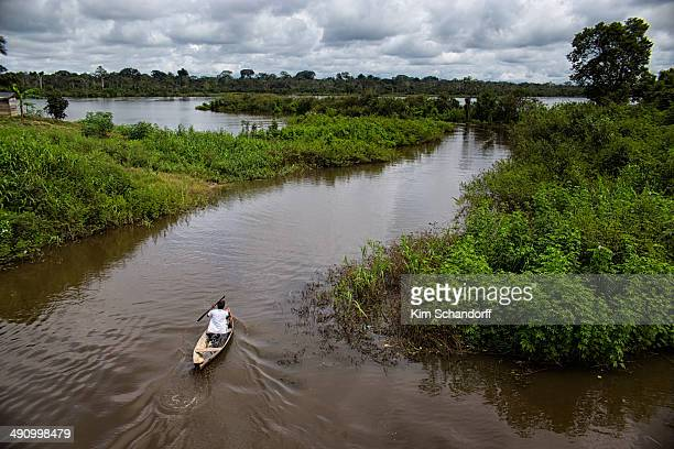 A man in his canoe heading for a lake in order to go fishing in one of the many small lakes along the Amazon river in Peru