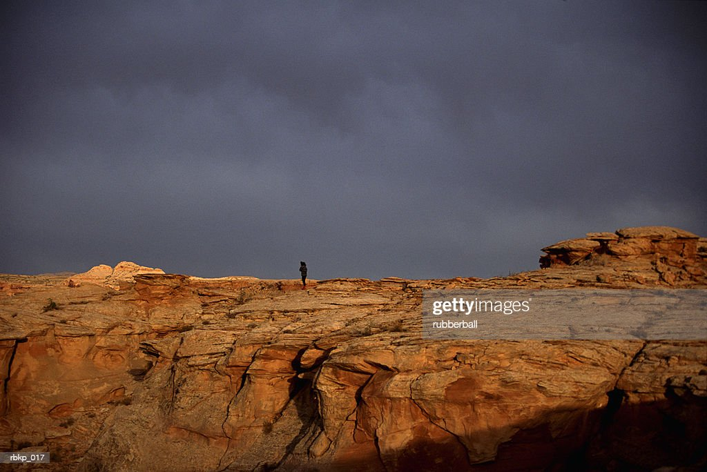 a man is hiking along a large mountain ridge with a threatening storm in the background : Stockfoto