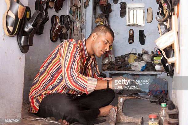 A man is reparing a shoe in his workshop. Is sitting down the ground. There are plenty of shoes around him. He is wearing a moked colored shirt.