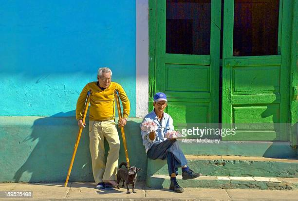 A man on crutches and another man with a pink iced cake in each hand wait, with a small black dog, outside a colorful door.