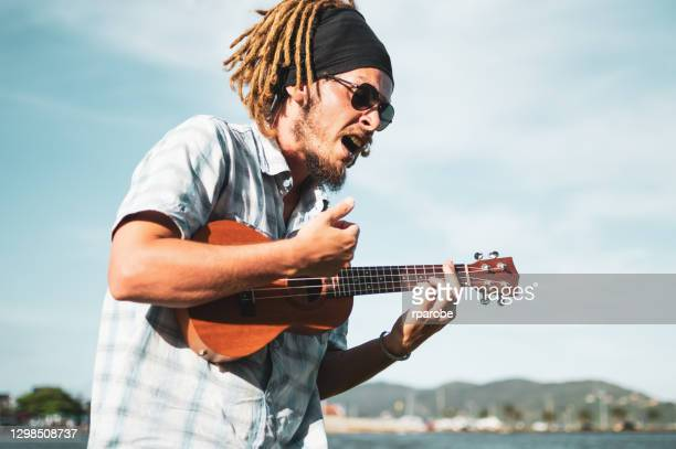a man playing ukulele and singing, in florianopolis - acoustic guitar stock pictures, royalty-free photos & images