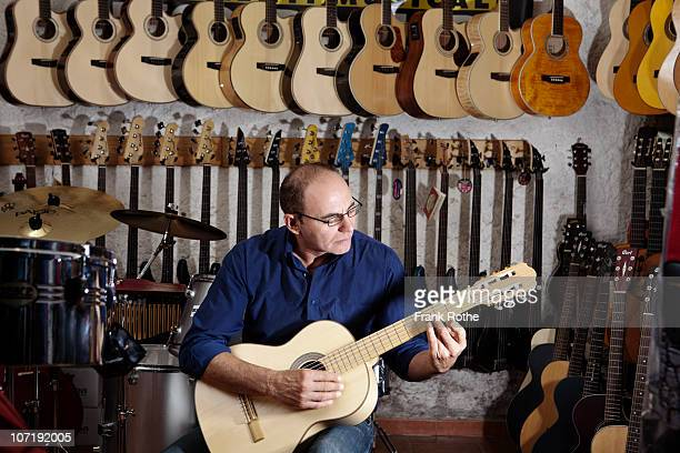 a man plays the guitar in a music store - musical equipment stock pictures, royalty-free photos & images