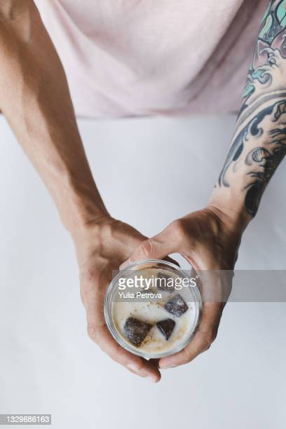 a man prepares a cold coffee drink with ice and milk, whips up milk - coffee drink stock pictures, royalty-free photos & images