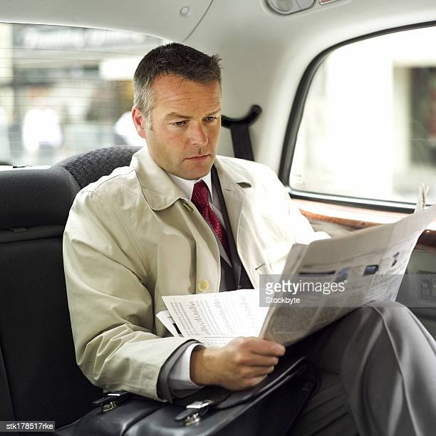 a man sitting in a car and reading a newspaper