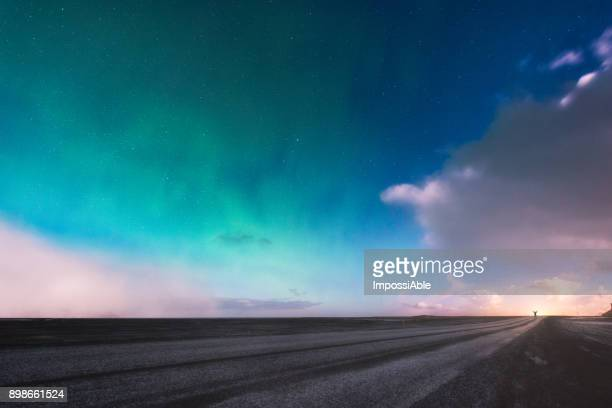 a man standing at the end of the road under aurora borealis display over his head, iceland no.1 ring road - moody sky stock pictures, royalty-free photos & images