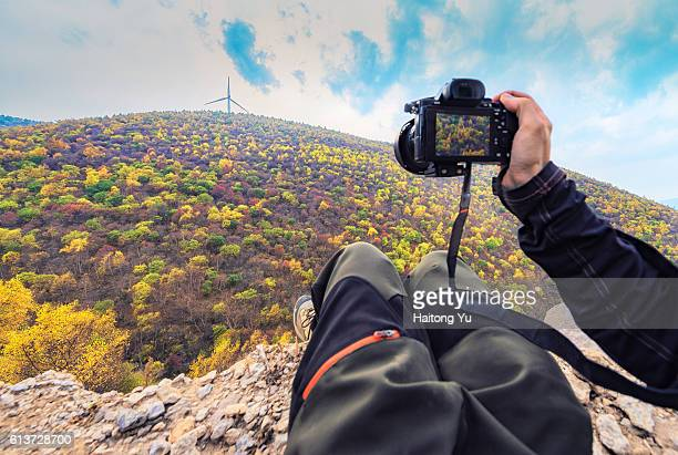 POV of a man using a mirrorless camera to take pictures of autumn landscape.