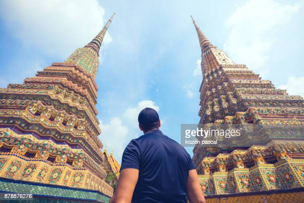 a man visiting wat pho temple in Bangkok in day , Thailand , Asia